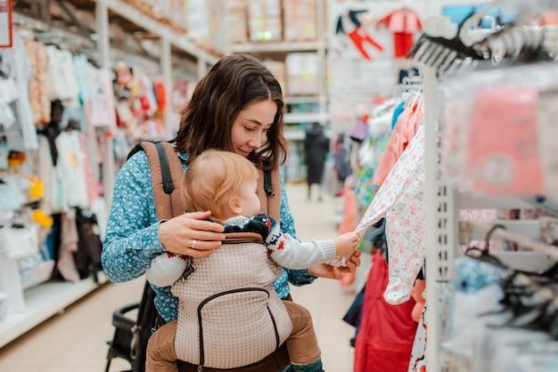Jonge moeder met babyzoon die in supermarkt winkelen