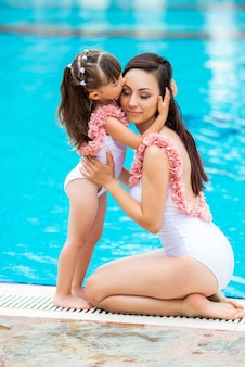 Jonge moeder met dochtertje in dezelfde witte zwemkleding zittend aan de rand van het zwembad. liefde en kus.