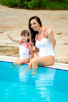 Jonge moeder met dochtertje in dezelfde witte zwemkleding zittend aan de rand van het zwembad.