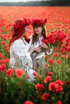 Jonge moeder met dochtertje verzamelt rode papaverbloemen in een bloeiend veld van dichtbij