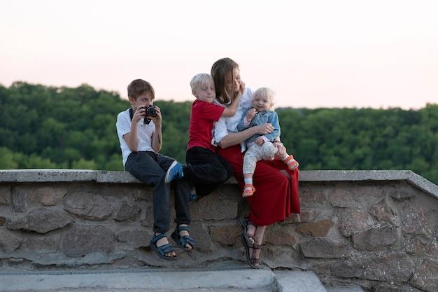 Jonge moeder met drie kinderen rust in de buurt van bos. reizen met kinderen. gelukkig gezin.