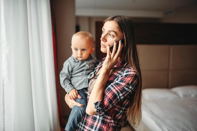 Jonge moeder met een baby in haar armen en binnenshuis praten aan de telefoon.
