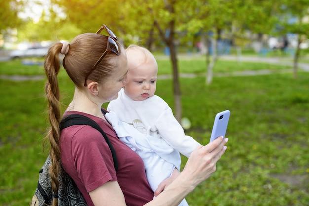 Jonge moeder met een baby in haar armen met behulp van een smartphone