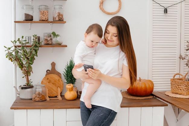 Jonge moeder met een baby in witte kleren in de keuken kookt drankjes uit een mok met smartphone