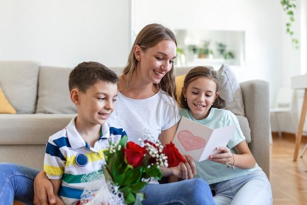 Jonge moeder met een boeket rozen lacht, knuffelt haar zoon en heerful meisje met een kaart en rozen feliciteert moeder tijdens vakantieviering in de keuken thuis. moederdag