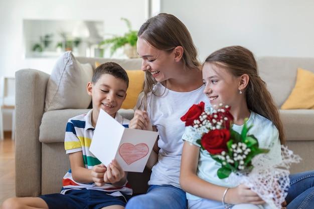 Jonge moeder met een boeket rozen lacht, knuffelt haar zoon, en heerful meisje met een kaart en rozen feliciteert moeder tijdens vakantieviering thuis. moederdag