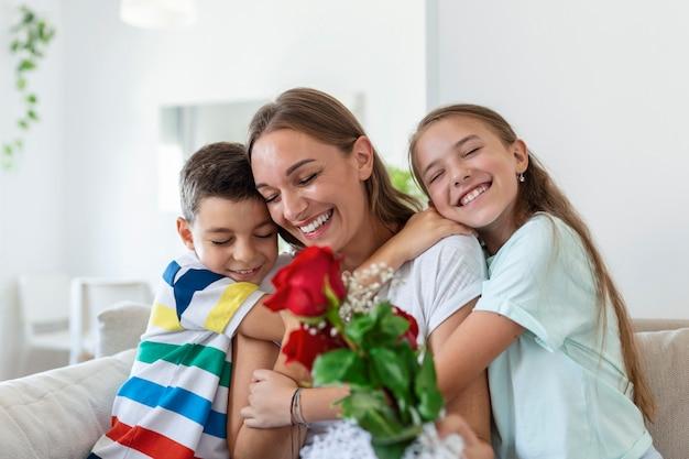 Jonge moeder met een boeket rozen lacht, knuffelt haar zoon en heerful meisje met een kaart feliciteert moeder tijdens vakantieviering in de keuken thuis