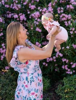 Jonge moeder met een jurk met bloemen die haar kleine babymeisje vasthoudt