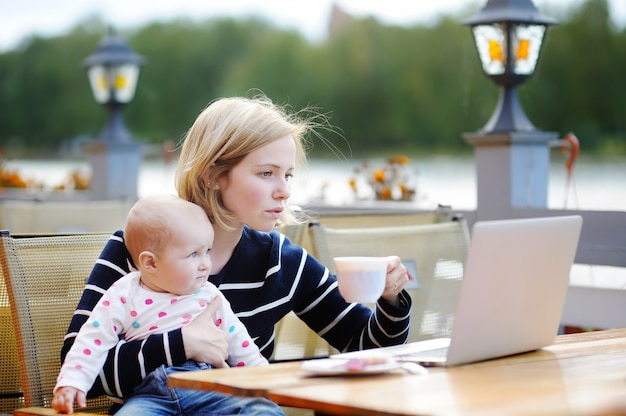 Jonge moeder met haar aanbiddelijk babymeisje die of op laptop in openluchtkoffie werken bestuderen
