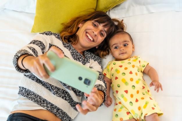 Jonge moeder met haar baby die een selfie maakt in haar slaapkamerbed, voor het eerst blank met haar vier maanden oude baby, familie thuis