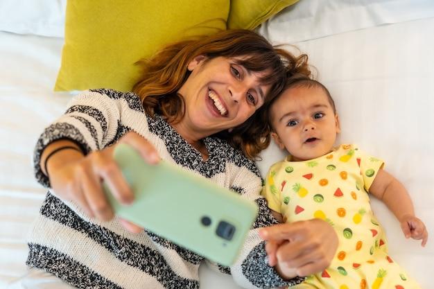 Jonge moeder met haar baby die een selfie maakt met de mobiele telefoon op het bed in haar slaapkamer, familie thuis