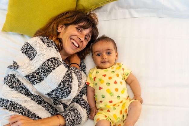 Jonge moeder met haar baby op het bed in haar slaapkamer, levensstijlportret van een jonge moeder, familie thuis