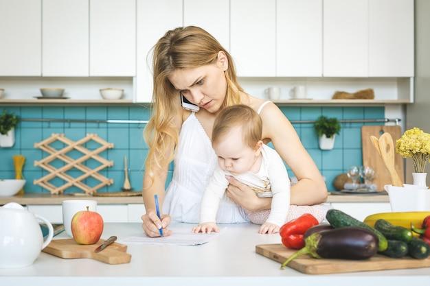 Jonge moeder met haar babydochter in het moderne keuken plaatsen. jonge aantrekkelijke kokvrouw wanhopig in vermoeide spanning ,.