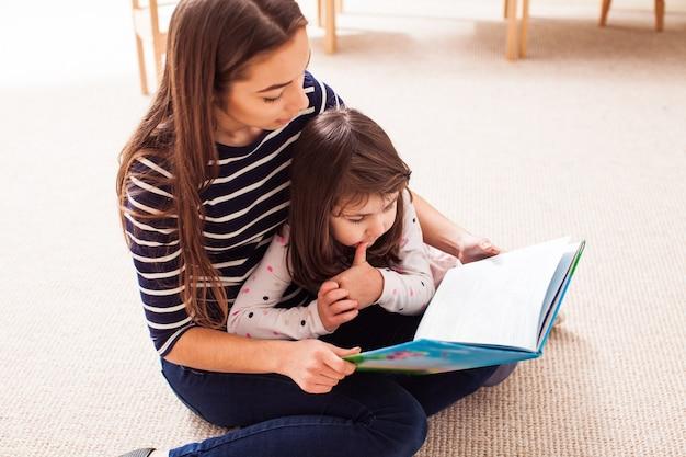 Jonge moeder met haar dochter die een boek leest dat op de grond zit