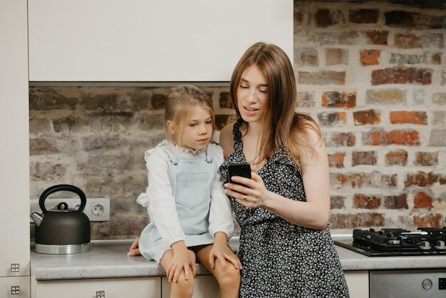 Jonge moeder met haar dochter in de keuken