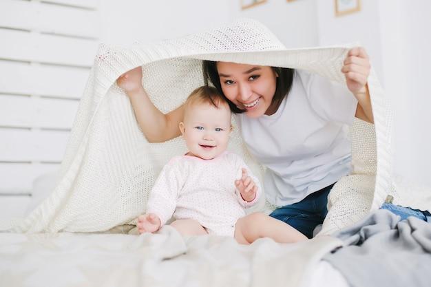 Jonge moeder met haar dochter speelt verstoppertje in de slaapkamer