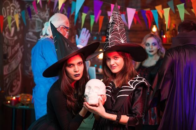 Jonge moeder met haar dochter verkleed als heksen op een halloween-feest. vrolijk meisje met grote heksenhoeden.