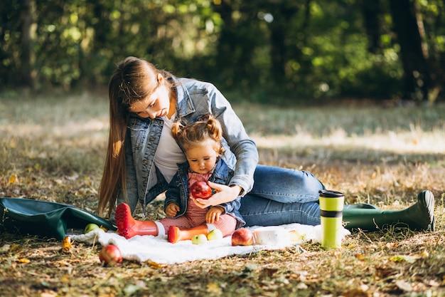 Jonge moeder met haar dochtertje in een herfst park met picknick
