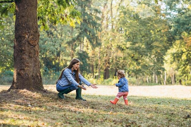 Jonge moeder met haar dochtertje in een herfst park
