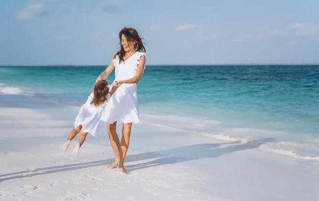 Jonge moeder met haar dochtertje op het strand aan de oceaan
