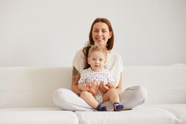 Jonge moeder met haar één jaar oude zoontje gekleed in pyjama's zijn ontspannend