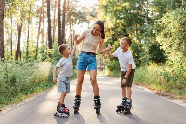 Jonge moeder met haar kinderen skaten in het zomerpark, haar zoons armen vasthoudend en vrolijk glimlachen, tijd doorbrengen en samen plezier hebben, familie die casual kleding draagt.