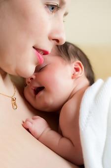 Jonge moeder met haar pasgeboren baby liggend op haar borst