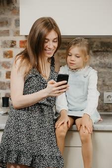 Jonge moeder met haar schattige dochter in de keuken