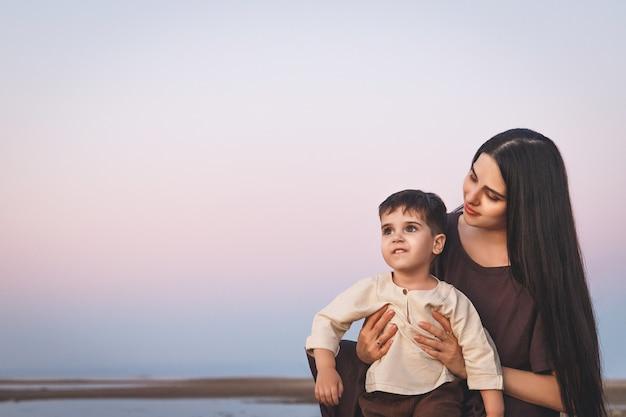 Jonge moeder met haar zoon van drie jaar oud die de zonsondergang op het strand bewondert family look linnen kleding