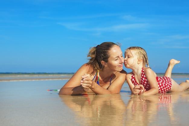 Jonge moeder met kind liggend in water op tropisch strand