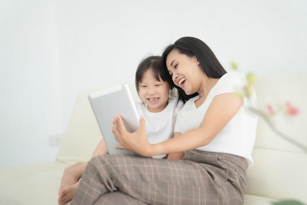 Jonge moeder met kinderen die digitale tablet samen thuis gebruiken. glimlachend gezin kijken naar scherm, speelgoed winkelen of cartoon online kijken,