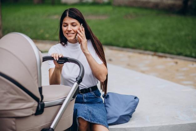 Jonge moeder met kinderwagen in park wandelen en praten over de telefoon
