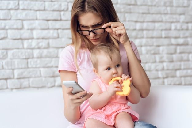 Jonge moeder met kleine baby met behulp van smartphone