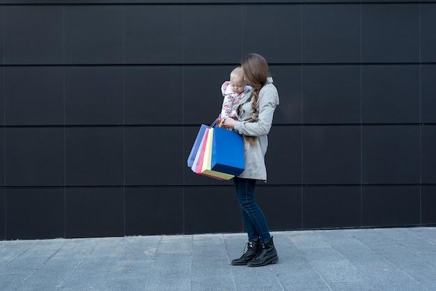 Jonge moeder met kleine dochter op de armen en boodschappentassen in de hand