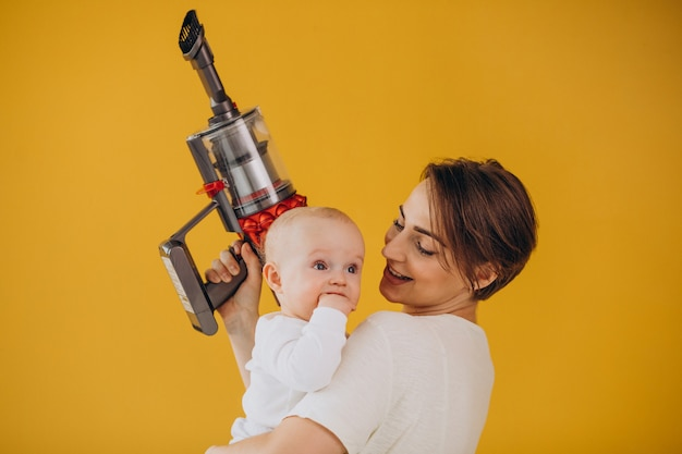 Jonge moeder met peuterzoon die thuis opruimt