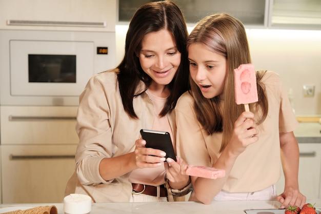 Jonge moeder met smartphone die haar verbaasde tienerdochter nieuwsgierige online video toont terwijl beiden zelfgemaakt ijs hebben