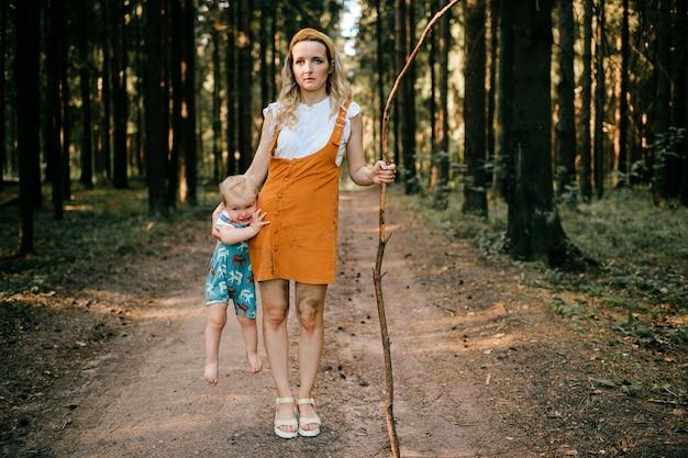 Jonge moeder met stok die haar zoon in het bos houdt