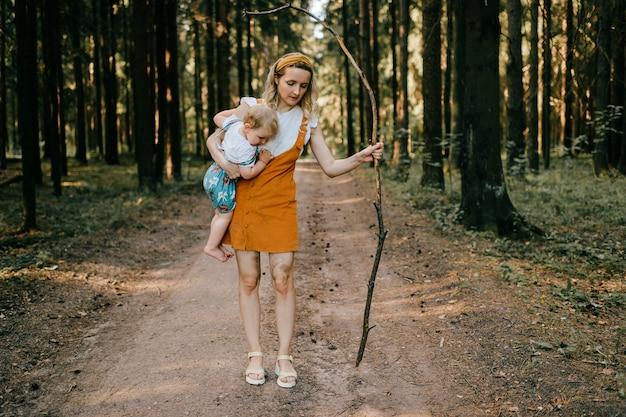 Jonge moeder met stok die haar zoon in het bos houdt Premium Foto