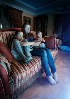 Jonge moeder met twee dochters die 's nachts horrorfilms kijken