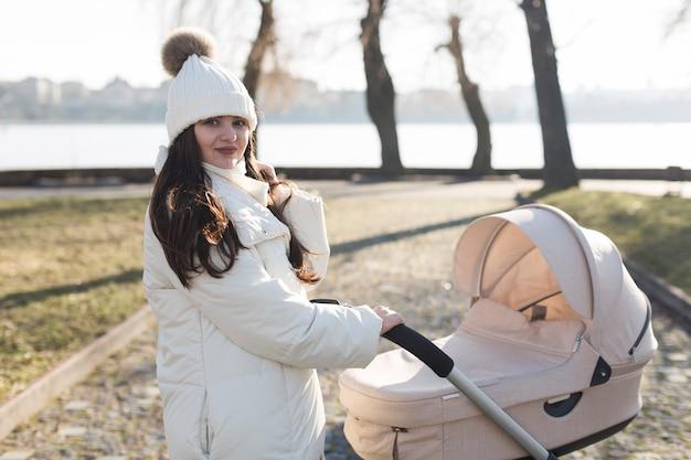 Jonge moeder met wandelwagen in park
