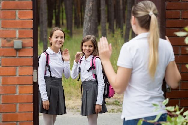 Jonge moeder neemt afscheid van haar dochters die naar school gaan