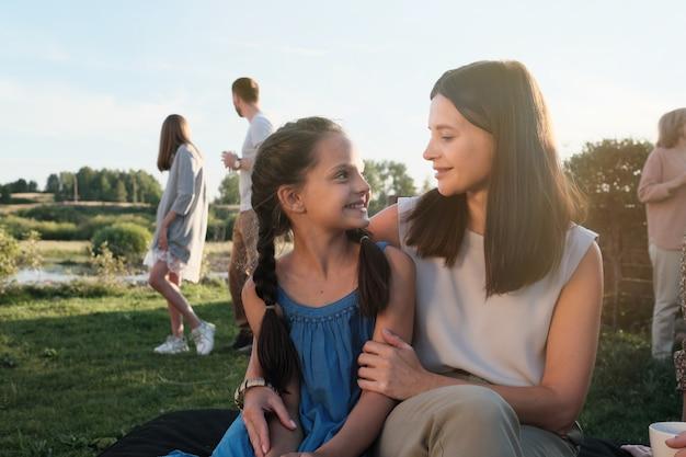 Jonge moeder omhelst en praat met haar dochtertje terwijl ze buiten in het land zit