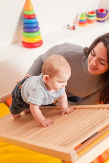 Jonge moeder ondersteunt de baby en helpt hem de ladder te beklimmen op de kleuterschool
