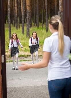 Jonge moeder ontmoet haar dochters na school in de deuropening