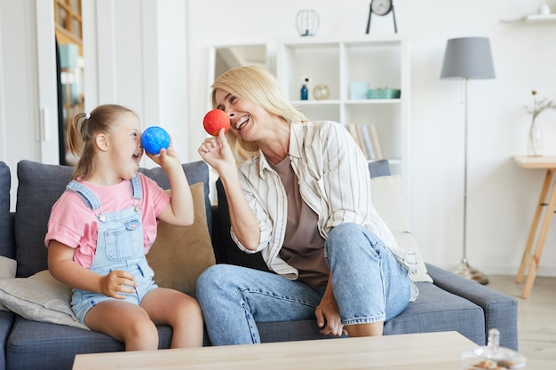 Jonge moeder plezier samen met haar dochter met het syndroom van down terwijl ze op de bank in de kamer zitten