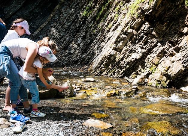 Jonge moeder probeert haar dochter te helpen haar schoenen uit te trekken om haar voeten in de bergstroom tijdens trekking nat te maken