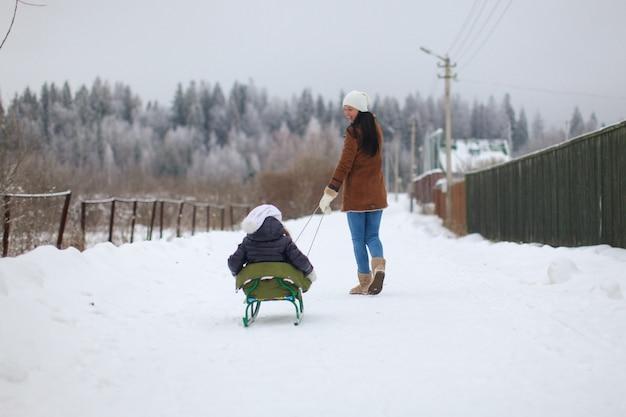Jonge moeder rolt haar kleine schattige dochters op een slee in de winterdag