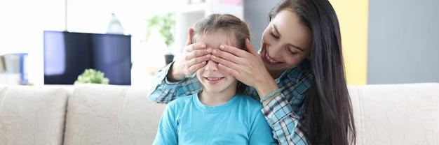 Jonge moeder sluit de ogen van haar dochter en geeft haar cadeau
