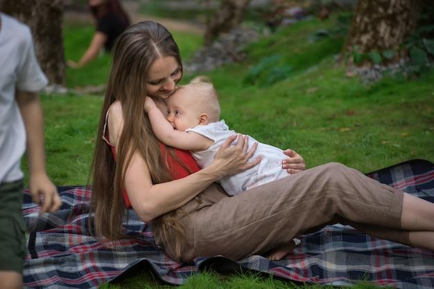 Jonge moeder speelde met de baby en zittend op een picknickdeken. vakantie met kinderen buiten