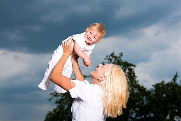 Jonge moeder speelt met haar baby in een stormachtig weer